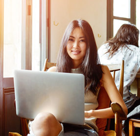 Study Australian courses online. Young woman in cafe studying.